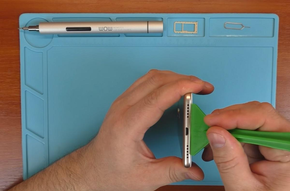 Использование пластикового инструмента для разбора телефона Xiaomi Redmi