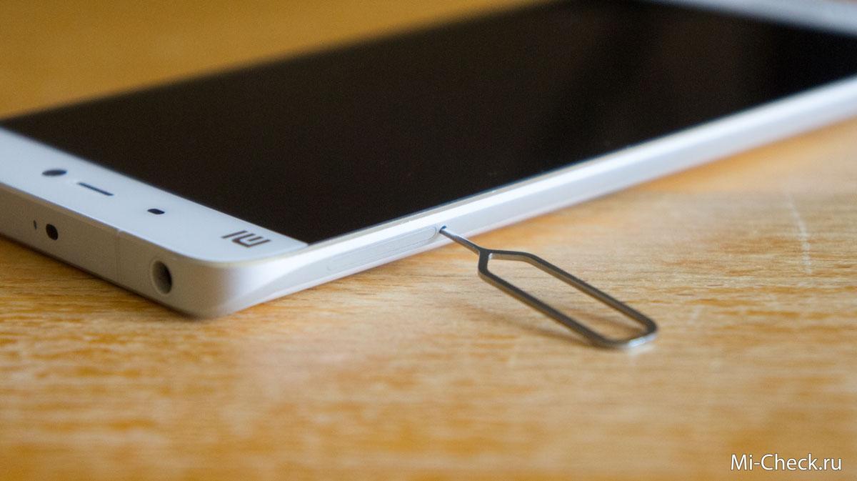 Вставьте инструмент в отверстие для извлечения лотка с SIM-картами